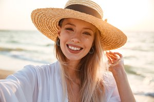 Delighted young girl in summer hat a