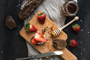 Black bread toasts with strawberries