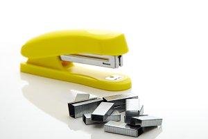 Yellow stapler on the white