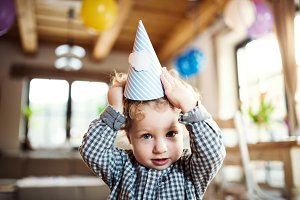 A toddler boy with a party hat