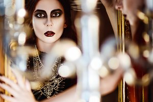 Beautiful goth girl looks in mirror