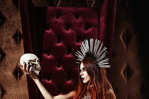 Beautiful goth girl holds skull