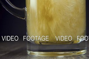 Slow motion pour light beer in a mug
