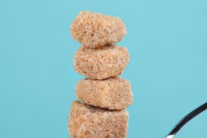 Raw Brown sugar cubes stacked on spo
