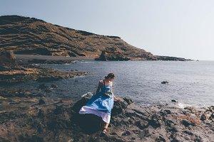 Woman sitting on rock beach