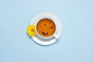 Cup of tea and yellow chrysanthemum