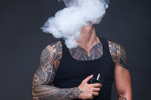 Vaper. The man with a muscular torso