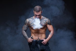 Vaper. The man with a muscular naked