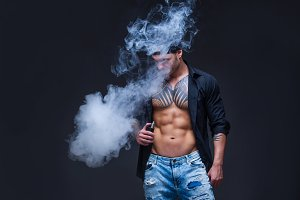 Vaper. The man dressed blue jeans