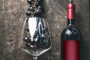Red wine bottle with glass and grape