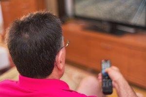 Back view of senior man watching tv