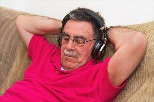 Senior man in headphones fall asleep