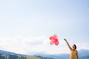 Young happy girl holding red balloon