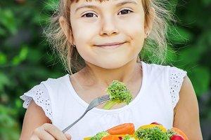 child eats vegetables. Summer photo.