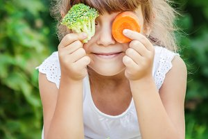 child eats vegetables. Summer photo.
