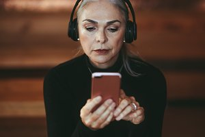 Senior businesswoman listening music