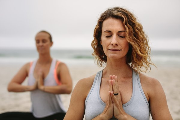 Women practicing meditation and yog…