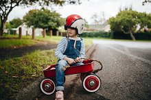 Beautiful young girl in a red wagon  by  in People