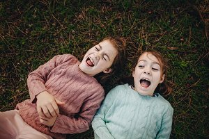 Twins sisters enjoying on the grass