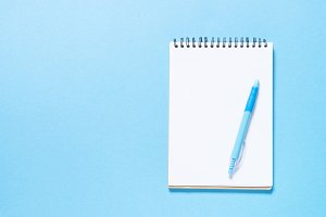 Notebook and pen on blue background.