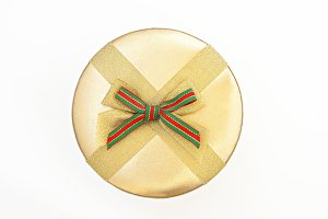 Round golden gift box with ribbon an