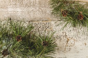 Pine branches with cones on a wooden