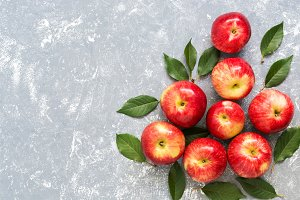 Red apples with leaves on a gray
