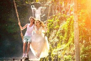 Young honeymoon couple swings in the