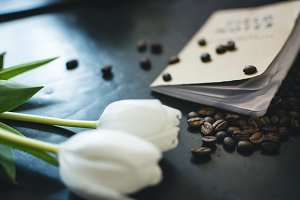 Spilled coffee beans, book and tulip