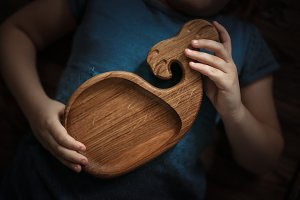 wooden plate form of whale, in hand