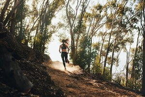 Woman trail running on a mountain