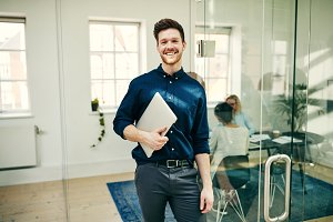 Smiling young businessman standing w