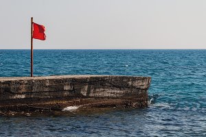Pier with a red flag in the sea