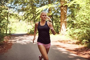 Fit young woman jogging alone on a f