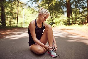 Fit woman tying up her running shoes