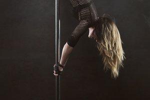 Pole dancer is hanging upside down o