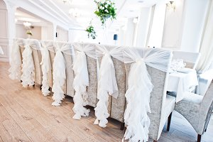 Wedding chairs with white ribbons at