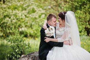 Lovely wedding couple sitting on big