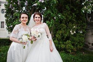 Bride with bridesmaid looking at cam