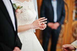 Bride puts wedding ring at hand on c