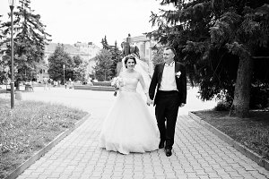 Happy wedding couple walking holding