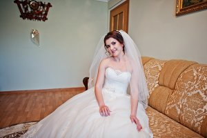 Tender brunette bride sitting on bed