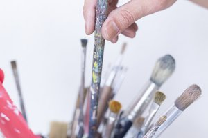 hand taking a paintbrush