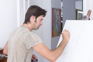 man drawing on canvas