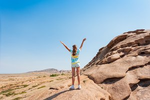 girl teenager standing on a rock hol