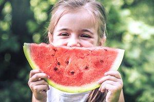 Little girl eats watermelon