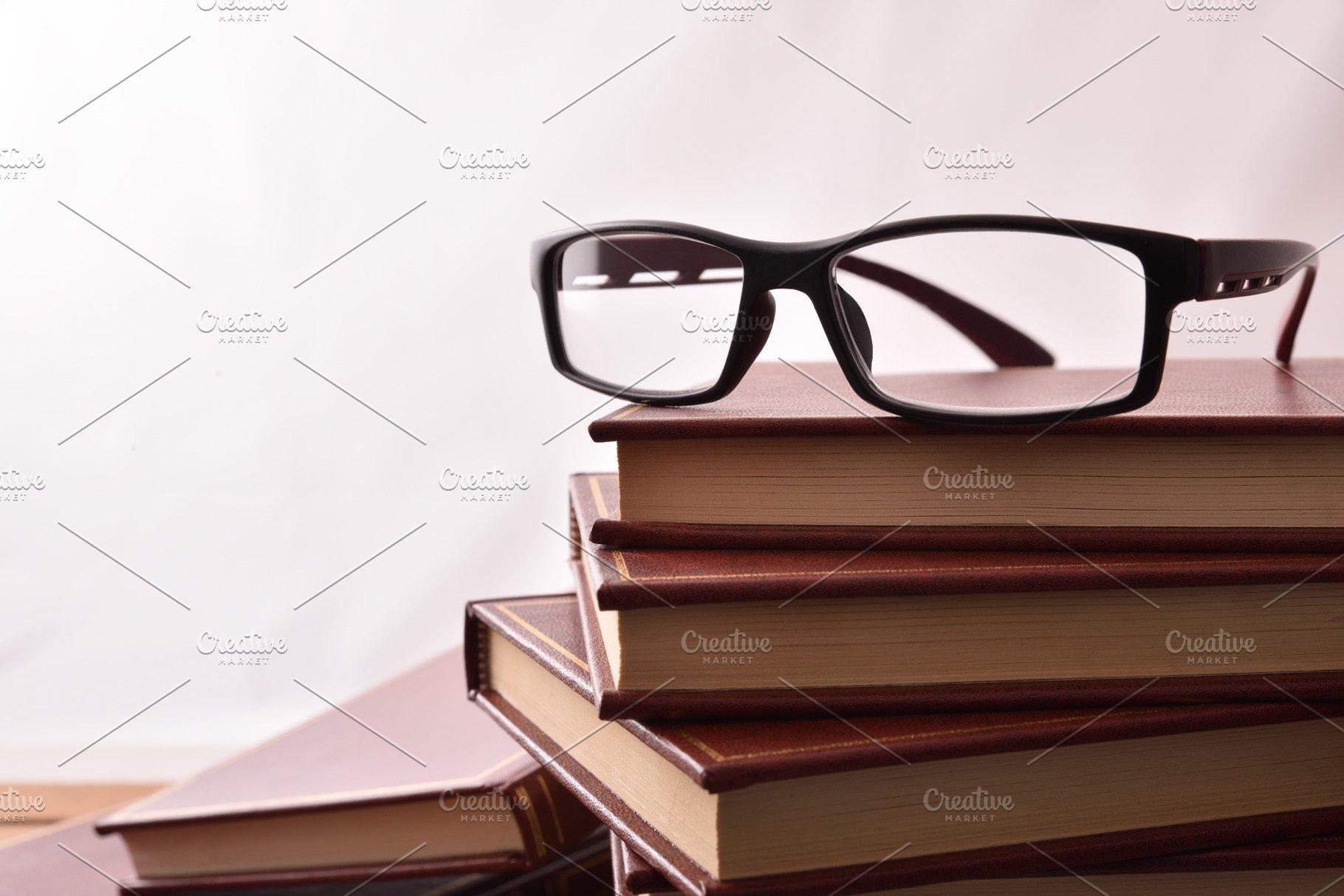 4da59f87ac9b Reading glasses on stack of books ~ Education Photos ~ Creative Market