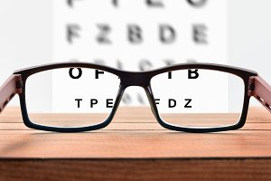 Glasses on table and alphabet letter