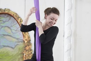 Young smiling aerialist hanging on