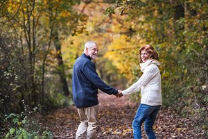 A senior couple walking in an autumn